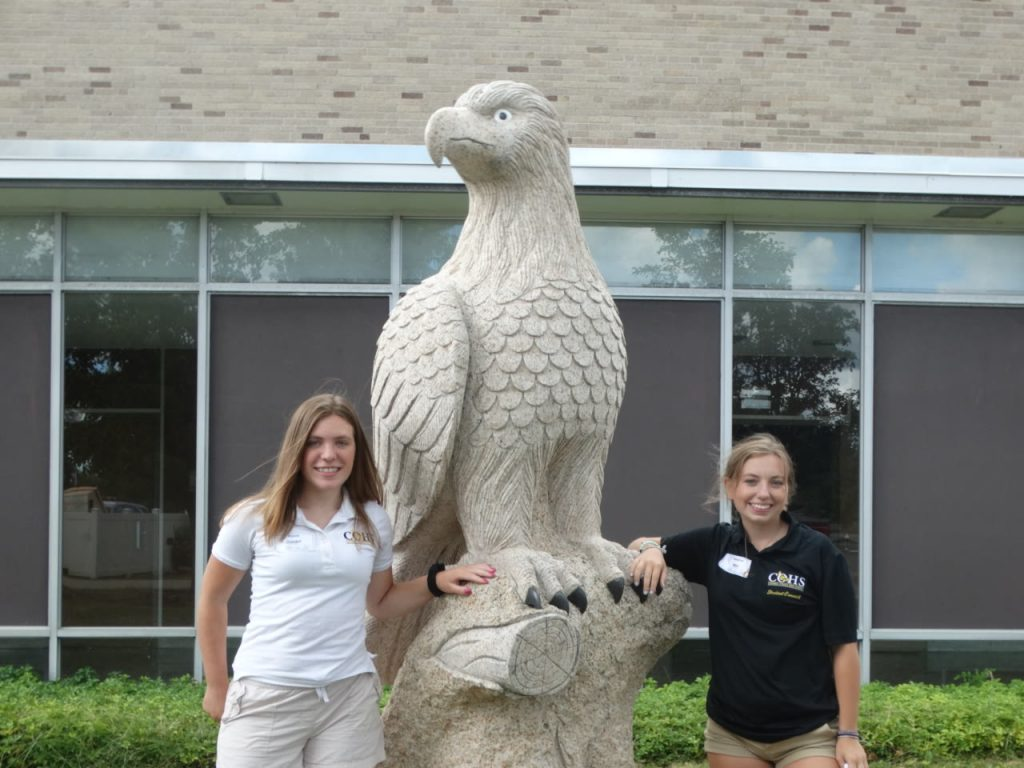 two female students stand next to a hawk statue
